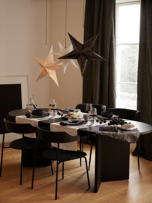 Woonkamer in beige met zwarte kerstdecoratie boven de zwarte tafel en zwarte fauteuls