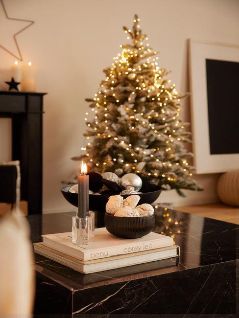 Kerstboom met verlichting naast een salontafel met dienblad en kaarsen