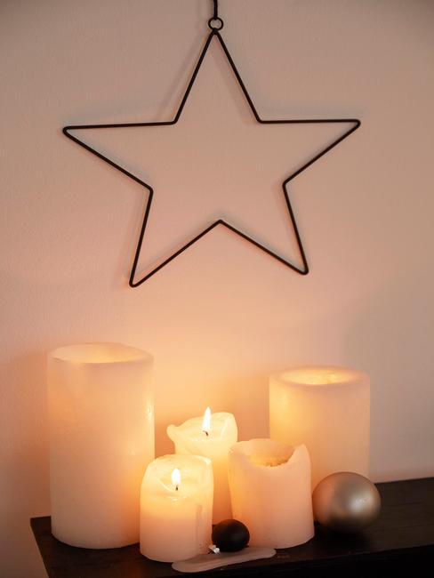 Kerstster boven kaarsen op de ladekast
