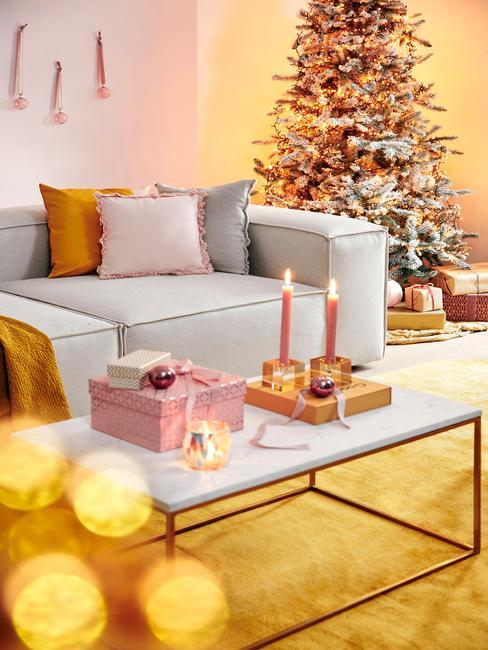 Salontafel in wit met witte zitbank en kleurrijke sierkussens en gele plaid naast een kerstboom