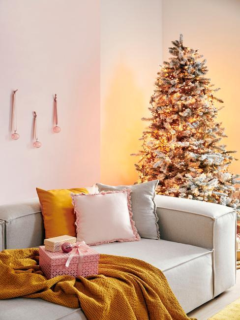Kerstdecoratie maken: woonkamer in wit met witte zitbank en kleurrijke sierkussens en gele plaid naast een kerstboom
