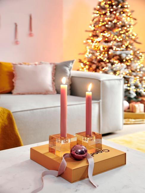 Kaarsen op witte salontafel naast een witte zitbank met sierkussens