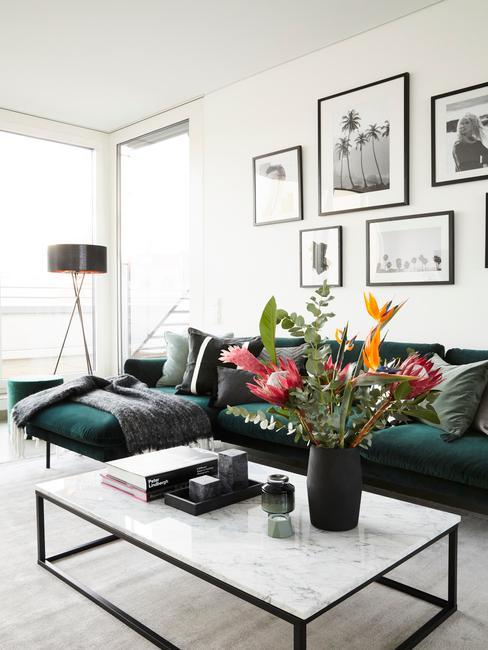 Salontafel decoratie: bloemen in zwarte vaas op marmeren salontafel in wit naast een groene bank
