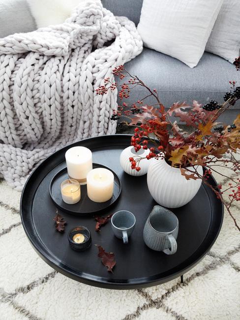 Zwart dieblad met kaarsen, koffiekopje en witte vaas met bloemen