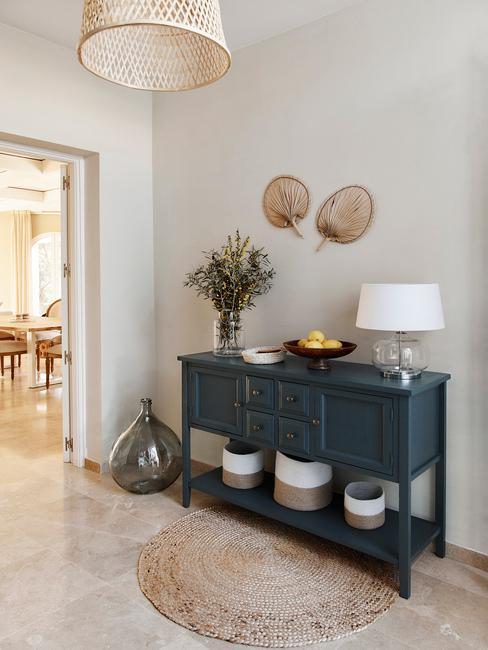 Dressoir met decoratieve objecten en een tafellamp met lampenkap in wit