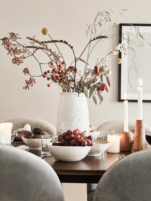 Witte vaas met bloemen op eettafel