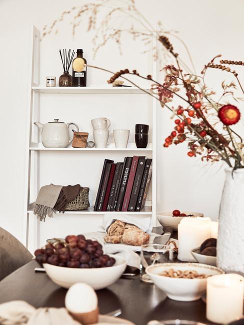 Tafeldecoratie-landelijk met een witte boekenkast met rode asseccoires