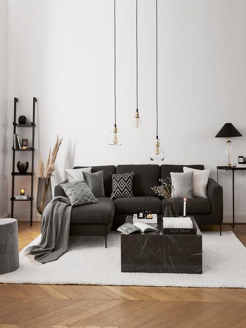 Koffietafelboek op marmeren salontafel in zwart naast een zitbank in grijs