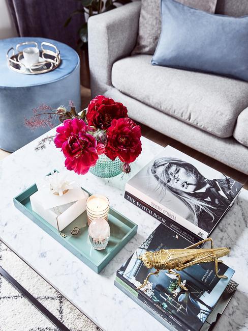 Koffietafelboek op marmeren salontafel in wit en grijs met glazen vaas met bloemen