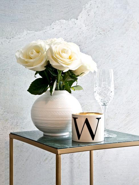 Witte vaas met bloemen naast en champagneglas op marmeren bijzettafel
