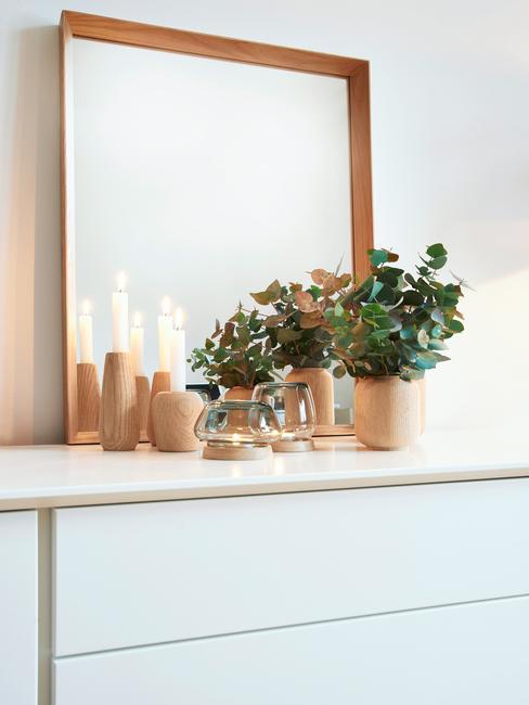 Houten decoratie op een wit dressoir met plantenpot naast een spiegel