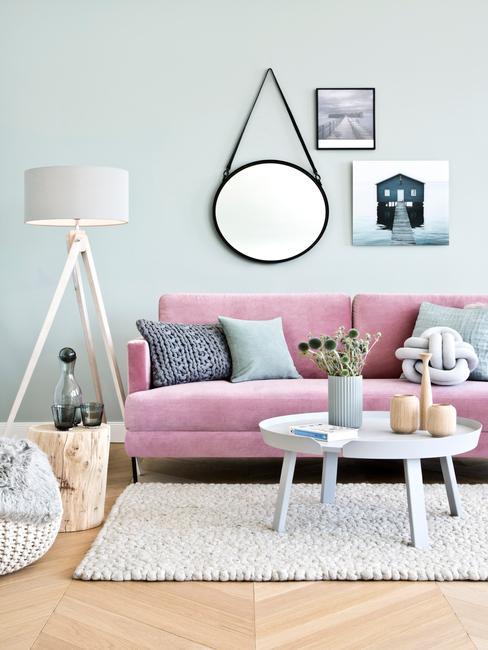 Houten decoratieve elementen in een woonkamer op een salontafel naast een roze zitbank