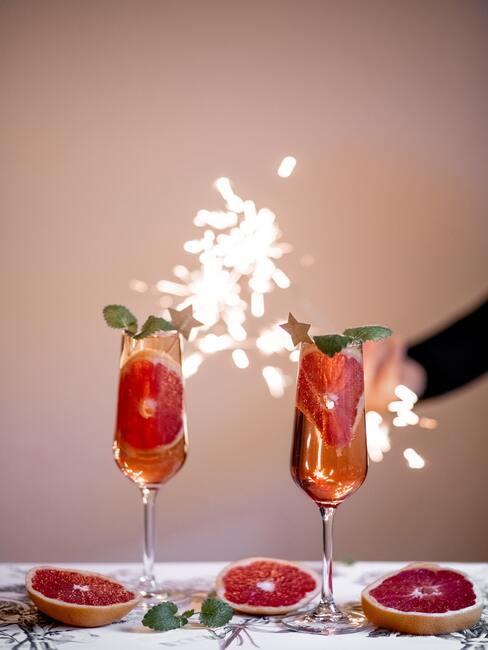 twee champagne glazen met cocktail en vuurwerk