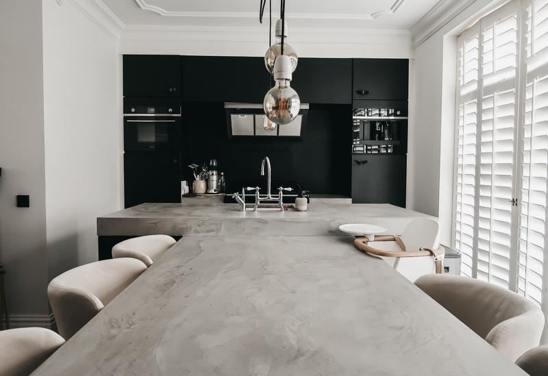 Grijze tafel in betonlook en zwarte keuken huis manon tilstra