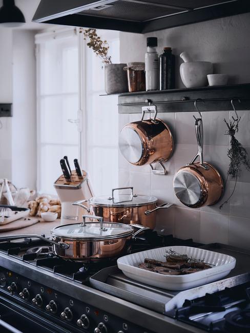 mat zwarte keuken met koperen pannen