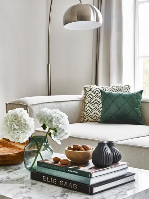 salontafel-decoratie met boeken en een blauwe vaas en een beige bank