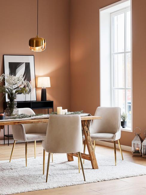 Eettafel-decoratie in het zwart op een houten ronde tafel met beige stoelen en gouden poten