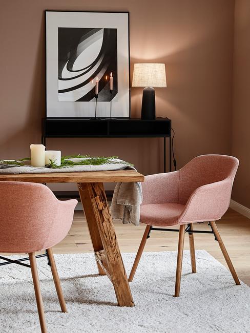 Eettafel-decoratie met witte kaarsen en een groen tafelkleed op een houten tafel met roze stoelen