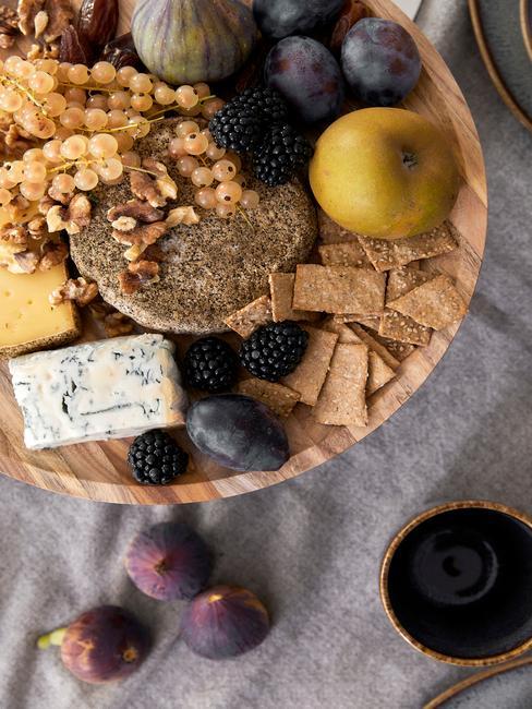 Plateau met verse kaas, fruit en rieten mand