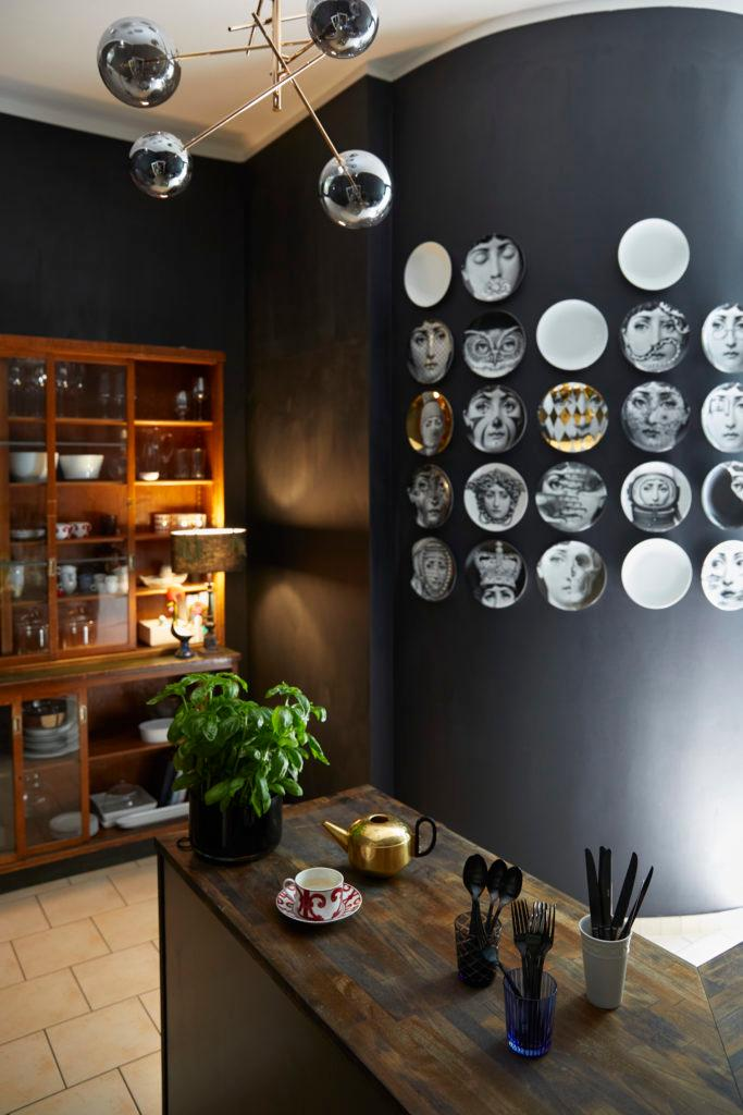 Zwarte muur met wandborden met 60ies print