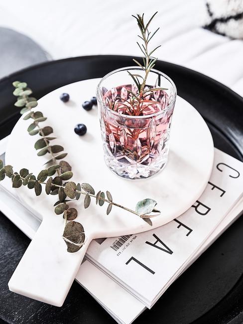 Een glas op bord met decoratie takken