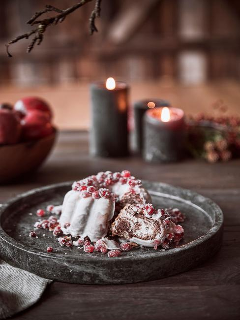 Een taart op houten tafel naast kaarsen en fruitmand