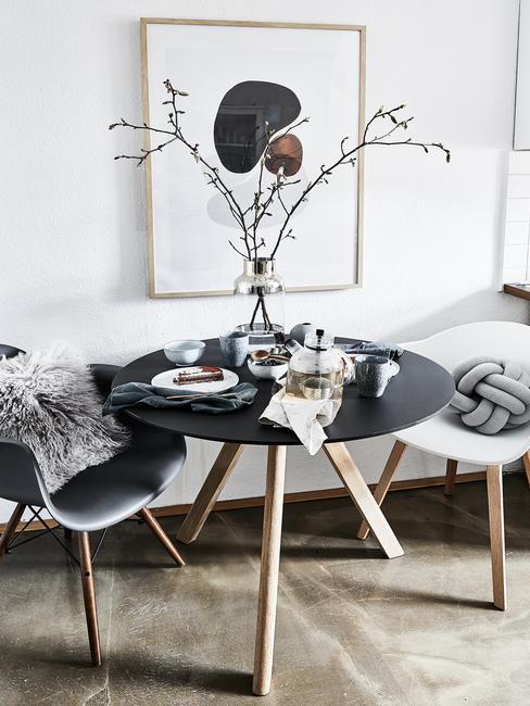 Grote glazen vaas met decoratie takken op zwarte eettafel met houten poten en stoelen in wit en grijs