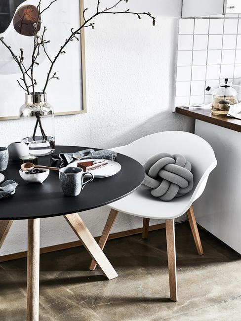 Eettafel in zwart naast stoel met sierussen