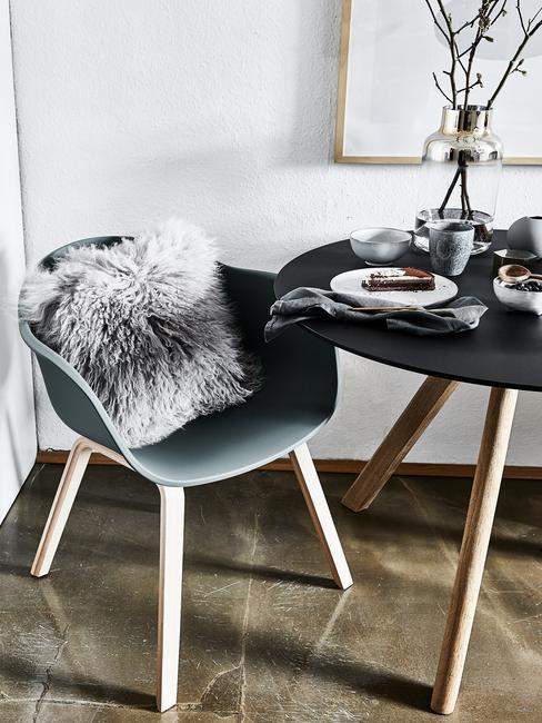Eettafel in zwart naast stoel met schapenvachten kussen