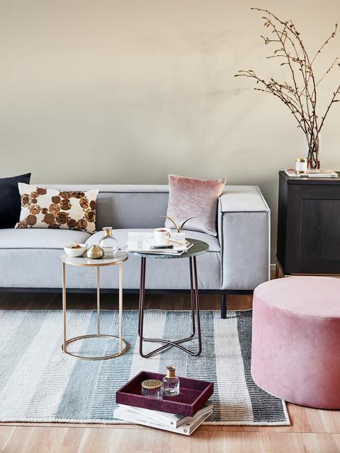 Woonkmaer in beige met comfortabele zitbank in grijs met sierkussens naast bijzettafels en vloerkleed in grijs