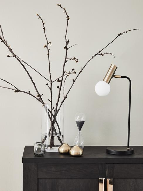 Tafellamp in goud en zwart op donkere dressoir naast een transparante glazen vaas