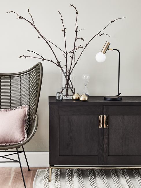 decoratie takken in transparante glazen vaas op donkerbruine dressoir naast een rotan fauteuil met sierkussen in roze