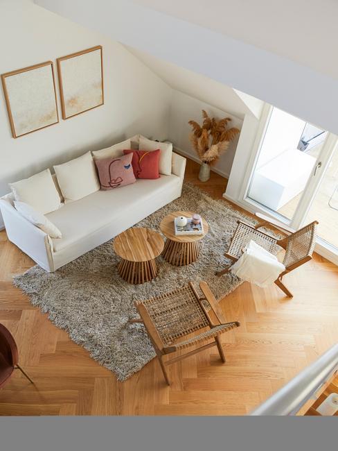 woonkamer met hoogpolig grijs tapijt en ronde licht houten tafels