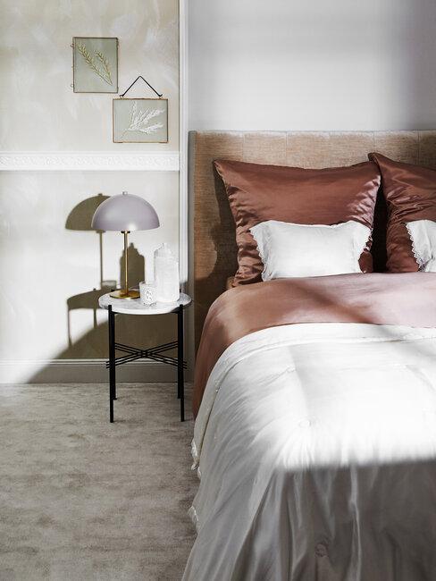 slaapkamer met wit marmeren bijzettafel en beddengoed in nude kleuren