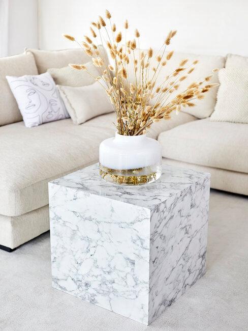 Witte hoekbank met vierkanten wit marmeren bijzettafel en droogbloemen