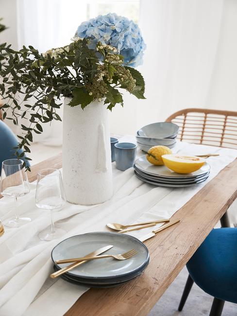 Houten eettafel met tafelkleed in wit en lichtbaluwe serviesset, witte vaas met bloemen