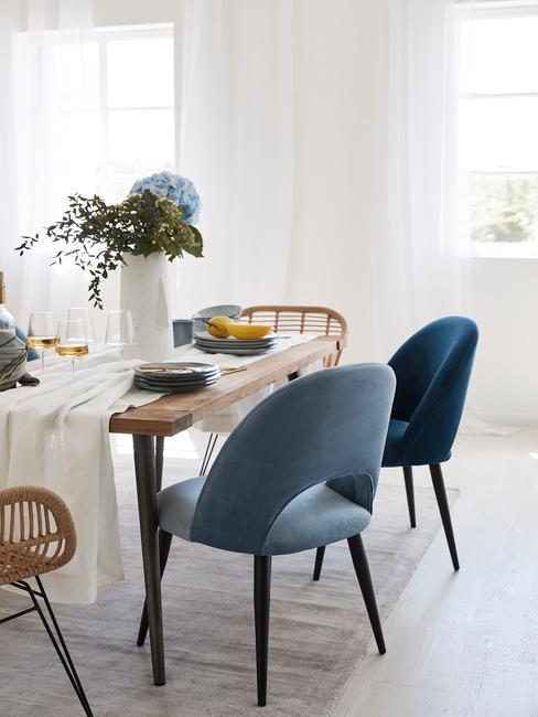 Houten eettafel met tafelkleed in wit en lichtbaluwe serviesset, witte vaas met bloemen en fluwelen stoelen in blauw