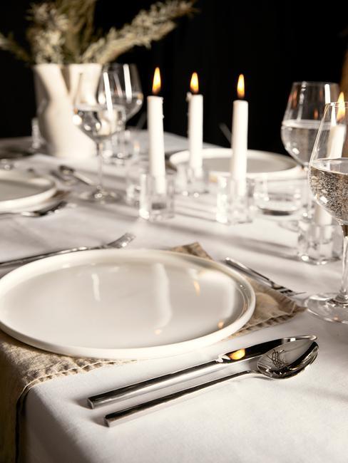 Gedekte tafel met witte serviesset en bestekset in zilver en witte kaarsen