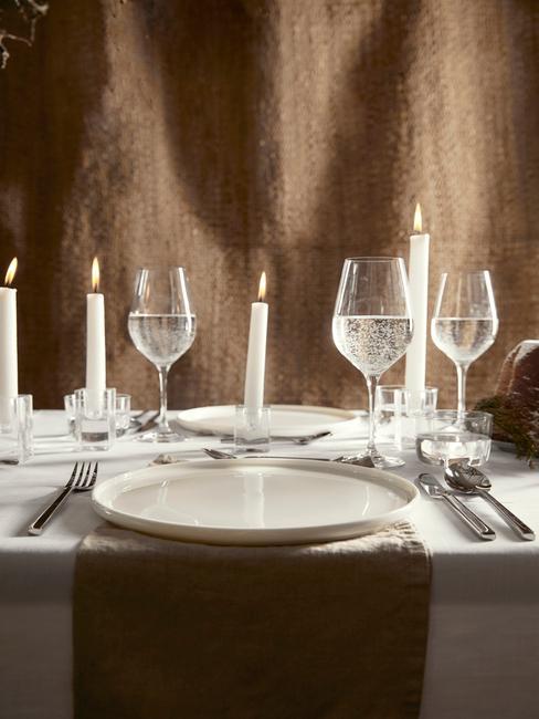 Wijnglazen op tafelkleed in wit en kaarsen