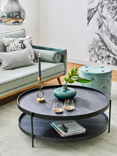 Grote salontafel in houten look met kaars en vaas naast een zitbank in turquoise kleur
