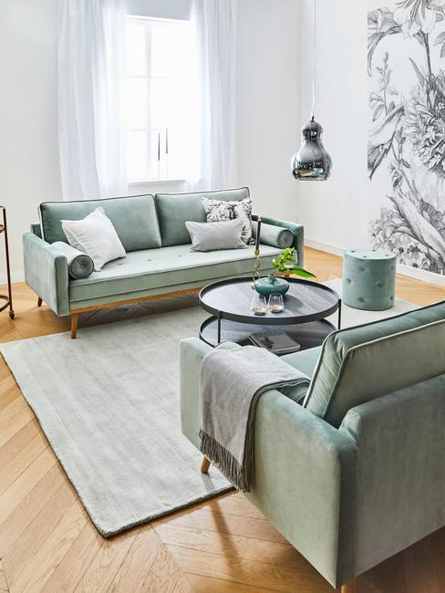 Lambrisering: grote salontafel in houten look met kaars en vaas naast een zitbank in turquoise kleur