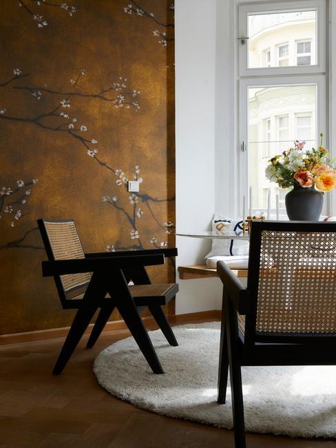 Lambrisering: rotan fauteuils naast een tafel met vaas met bloemen