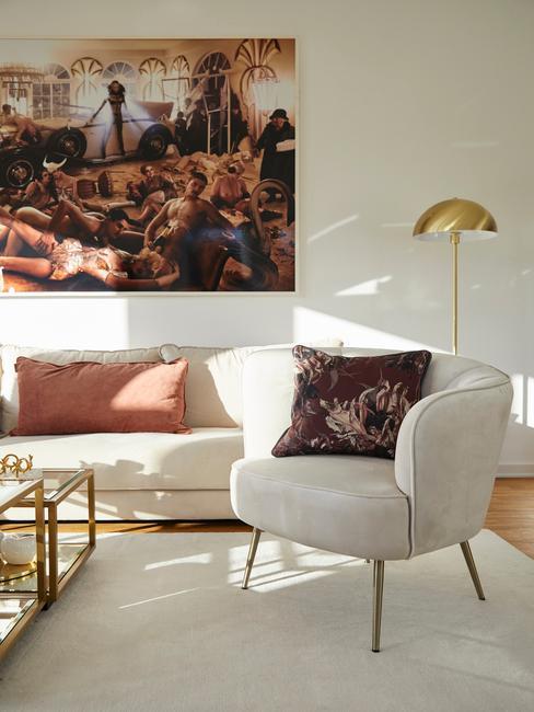 Schilderij op witte muur, witte fauteuil, comfortabele zitbank in wit