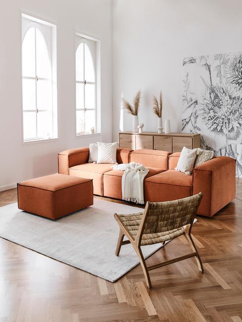 Hollandse meesters: woonkamer in wit met oranje zitbank met sierkussens en rotan fauteuil op vloerkleed in wit