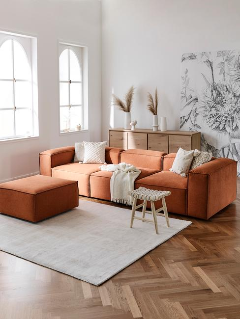 Woonkamer in wit met oranje zitbank met sierkussens en rotan fauteuil op vloerkleed in wit