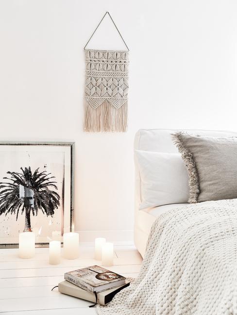 Slaapkamer in wit met groot bed en witte bedlinnen en decoratief muurobject