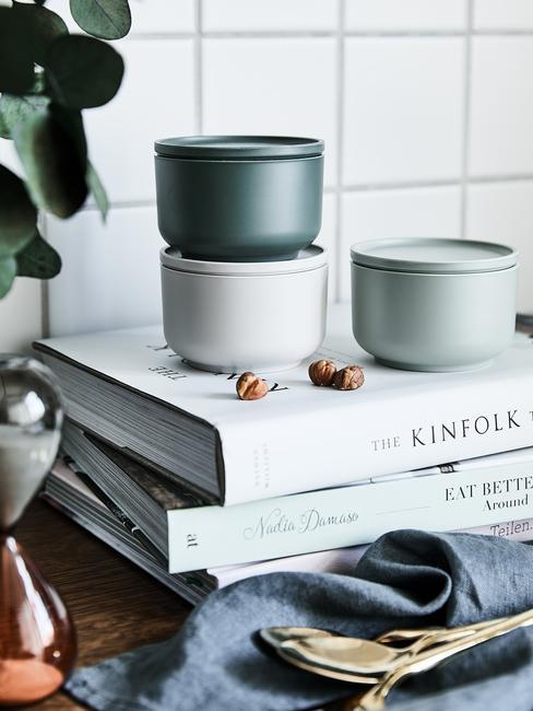 scandinavische keuken met groene opbergbakjes en stapel kookboeken