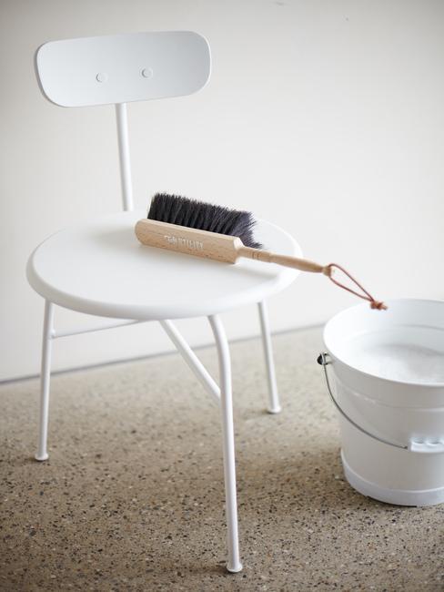 Witte keukenstoel op gegoten vloer met stoffer