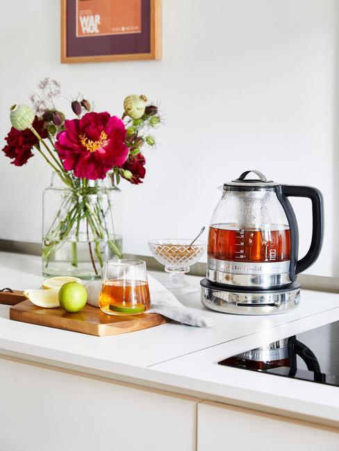 lichte keuken met licht aanrechtblad en theepot en vaas met verse bloemen
