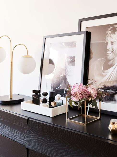 Zwarte dressoir met decoraties: kaarsen, dienbladen, tafellampen en ingelijste print